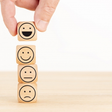 Customer service evaluation and satisfaction survey concept. Hand picked the happy face emoticon on wooden blocks